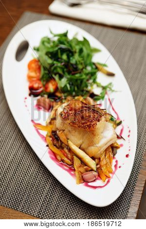 White fish fillet with vegetables on restaurant table