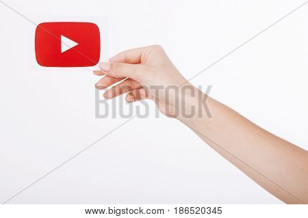 KIEV, UKRAINE - August 22, 2016: Woman hands holding paper with YouTube logotype icon printed on paper. YouTube is a video-sharing website headquartered in San Bruno, California.