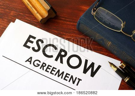 Document with title escrow agreement on a table.