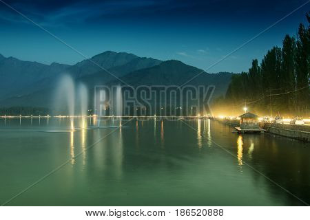 Fountains over the Dal Lake with mountains in the background at dusk. Dal Lake is the most famous lakes of Jammu and Kashmir India and is tourist attraction from all over the world.