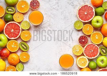 Citrus fruits frame vegan vitamin mix flat lay on white background, healthy vegetarian organic food, antioxidant detox diet. Tropical summer mix grapefruit, orange, apple, mandarin, sliced kiwi fruit