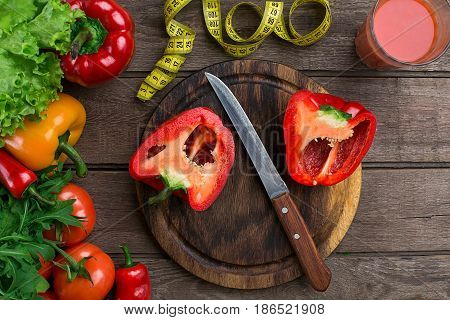 Glass of tomato juice with vegetables and measuring tape on wooden table close-up. On the cutting board is sliced pepper. Copy space. Top view