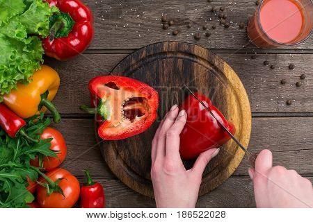 Female hands cutting pepper at table, top view. On the table leaves of lettuce, pepper, a glass of tomato juice, a wooden board and a knife