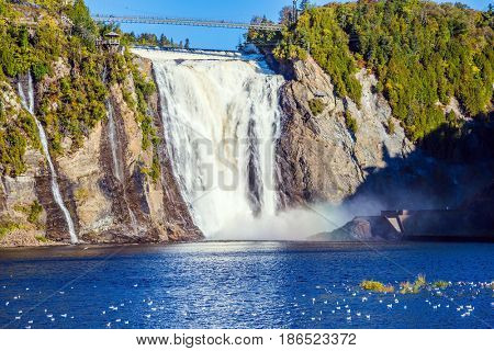 Montmorency Falls Park, close to the center of Old Quebec. Powerful waterfall Montmorency. Sunny autumn day. The concept of active and cultural tourism