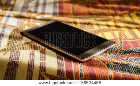 smartphone gold color lying on a blanket