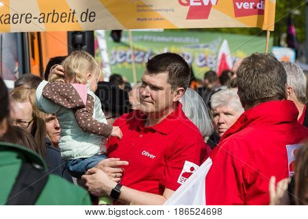 BERLIN - MAY 01 2016: A man with a child in her arms. Members of trade unions workers and employees at the demonstration on the occasion of Labour day.