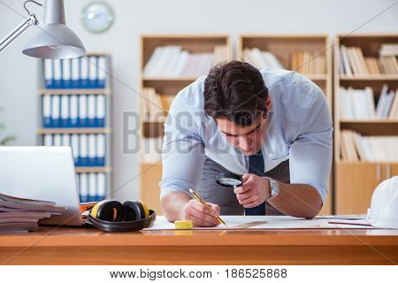 Engineer supervisor working on drawings in the office