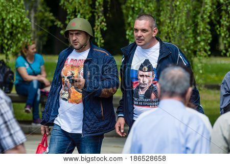 BERLIN - MAY 08 2016: Victory in Europe Day. Soviet War Memorial in Treptower Park. Patriotically dressed men - in an Soviet military helmet WWII a T-shirt with the image of Russian President Vladimir Putin.