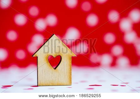 Wooden House With Hole In Form Of Heart On Red And White Background