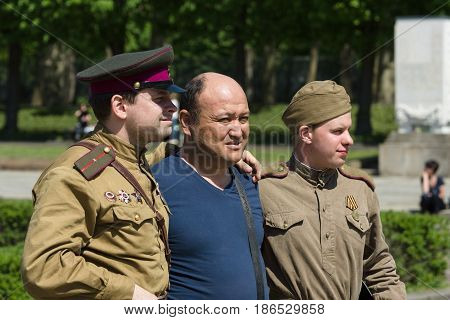 BERLIN - MAY 09 2016: Victory Day in Treptower Park. Visitors are photographed together with the Red Army officer and a soldier in the uniform of during the Second World War.