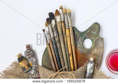 Brushes palette tubes with paint and thinner in a glass jar stand on white background