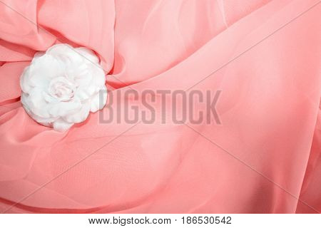 White textile rose and light red textile background