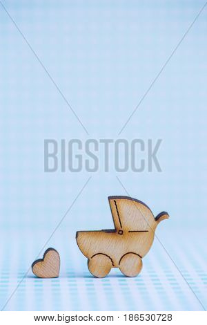 Wooden Icon Of Baby Buggy And Little Heart On Blue Checkered Background