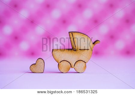 Wooden Icon Of Baby Buggy And Little Heart On Pink Spotted Background