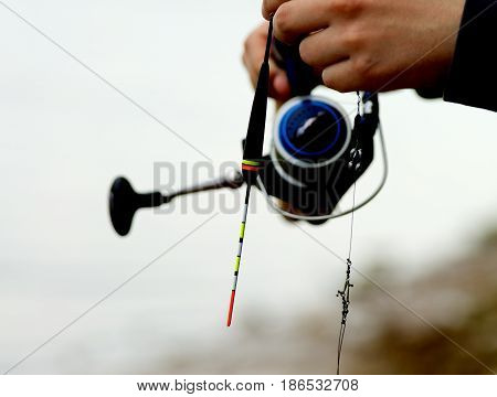 Man Holding Fishing Rod on Blurred Nature background Outdoors. Focus on Bobber