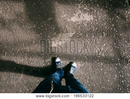 Point of view shot of a man look down to his feet standing on street