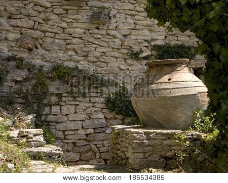 old earthen jug standing on a masonry near ancient stonewall