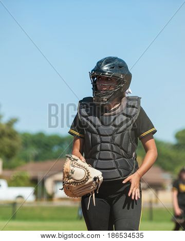 Softball catcher in black uniform with glove off of hand.