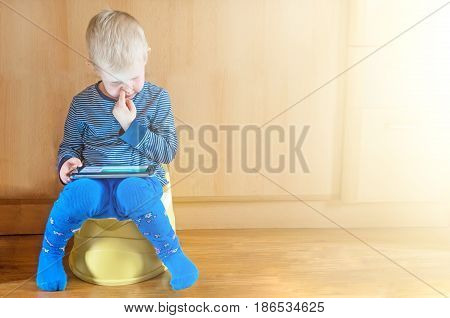 Little Boy On Potty With Tablet Pc On The White Carpet.