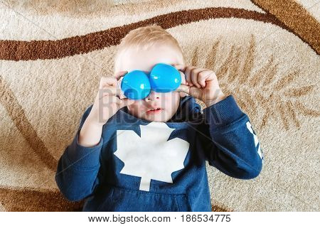 Boy lies on the floor and shows funny eyes with toys