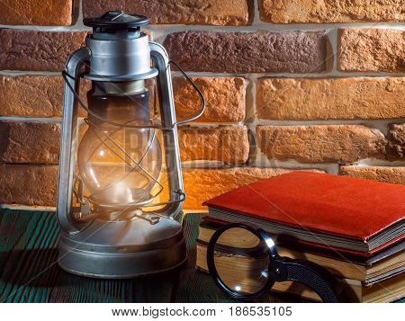 Still life kerosene lamp shines on  wooden desktop  stone brick background book camera