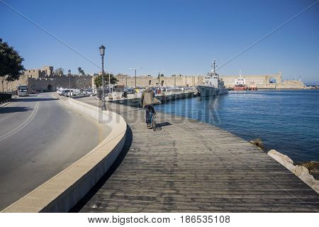 17TH FEBRUARY 2017, RHODES, GREECE - Male cyclist riding his bike away from viewer on the boardwalk at the port in the ancient city of Rhodes Greece