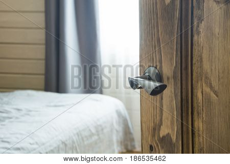 Open wooden door and view to the bedroom and bed. Blurred background.