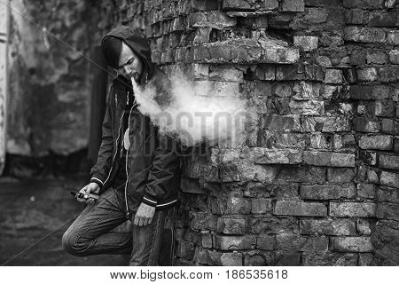 Vape Man. Photo Of A Handsome Young White Guy In The Hood Vaping And Letting Off Steam From An Elect