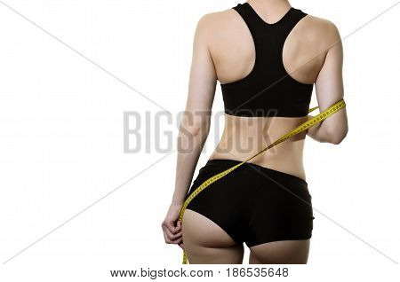 Slim Woman With A Measured Ribbon In The Back View On A White Background.