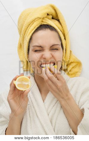 A girl in a dressing gown bites a lemon frown a yellow towel on her head