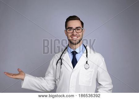 Handsome young doctor on grey background
