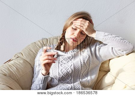 Young ill woman with electronic thermometer sitting on lounge at home