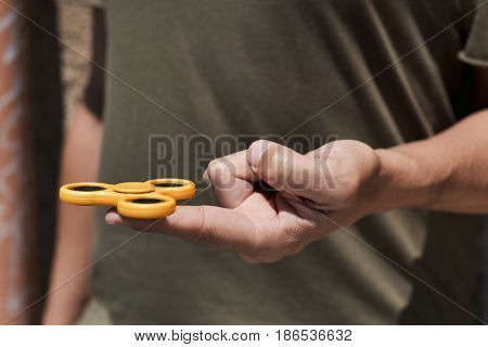 closeup of a young caucasian man playing with a yellow fidget spinner in the street
