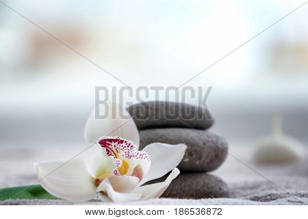 Beautiful spa composition with stones and flower on towel in modern wellness center