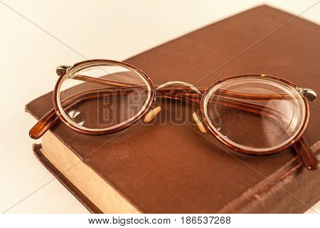Old grandmother's glasses and a dilapidated book closeup
