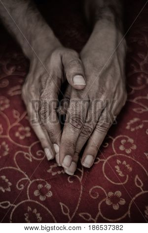Tanned hands of an adult Indian man lying on a red tablecloth