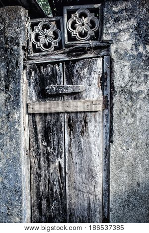Old ruined wooden door in a stone wall