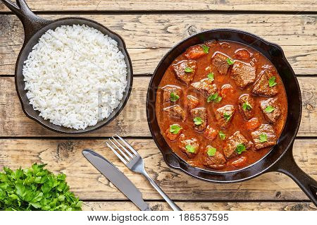 Goulash homemade Hungarian beef meat stew soup food cooked with spicy gravy sauce in cast iron pan meal served with rice and chopped parsley on rustic wooden texture kitchen table background.