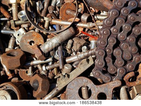 Mix of rusty auto scrap including nuts bolts and a chain. Background that can be used for text.