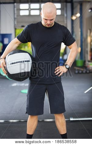 Determined and strong male athlete holding medicine ball in health club