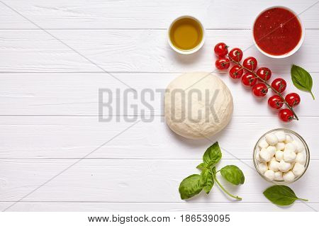 Raw pizza dough with baking pastry ingredients: mozzarella, tomatoes sauce, basil, olive oil, cheese, spices. Italian traditional pizza margherita preparation on white wooden table