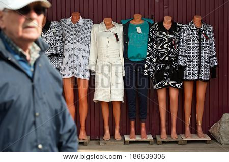 MOSCOW, RUSSIA - MAY 132017: An elderly man walks along the street past mannequins with women's clothes