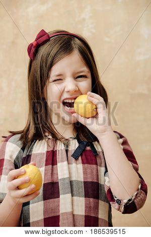 Kid Or Girl With Winking Eye Eating Lemons
