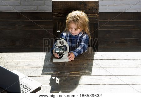 Educational Concept, Boy Student Studying At Workplace With Microscope, Laptop