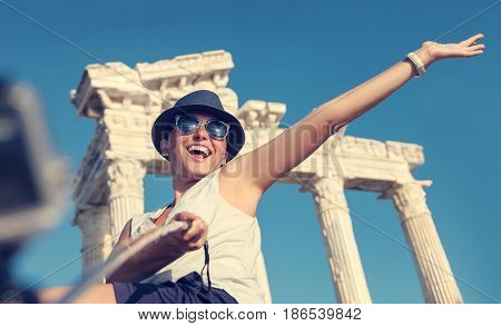 Happy smiling young woman take a selfie photo on antique sights view