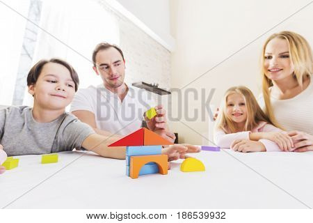 Family of four people with children constructing house of toy blocks, real estate concept