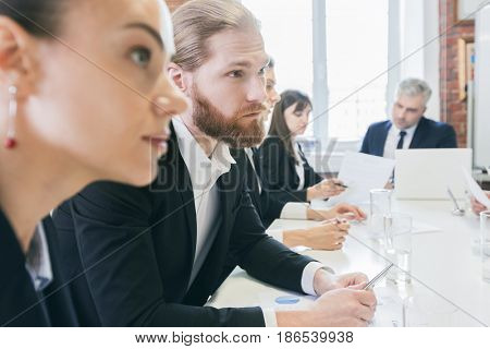 Business people sitting at the table in a row and work with documents