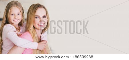 Portrait of beautiful young mother and daughter piggyback ride, photo with copy space