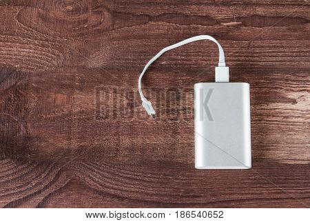 Grey Portable External Battery ( Power Bank ) With Usb Cable On Wooden Background