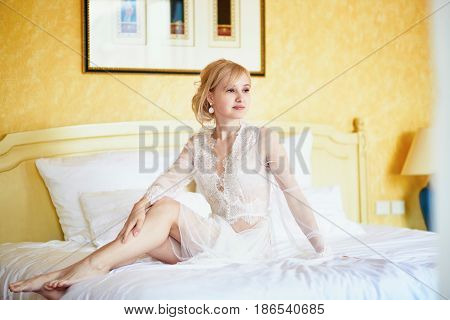 Woman In Elegant Lace Rest Gown Sitting On Bed At Early Morning